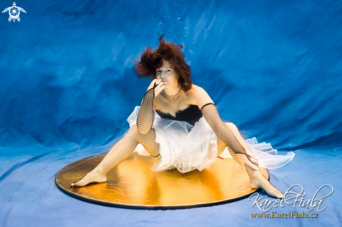 A human | woman sitting on a gold platter